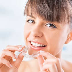 Woman placing her Invisalign tray