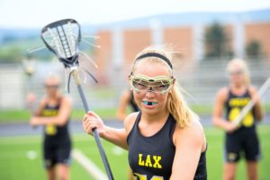 young athlete protecting her smile with a custom mouthguard